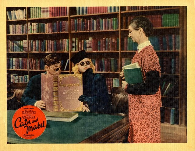 Lobby card for Cain and Mabel (1936) showcasing the library scene