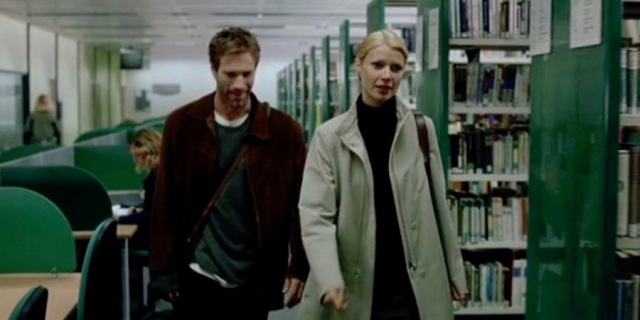 Maud and Roland walk through a library en route to Maud's office