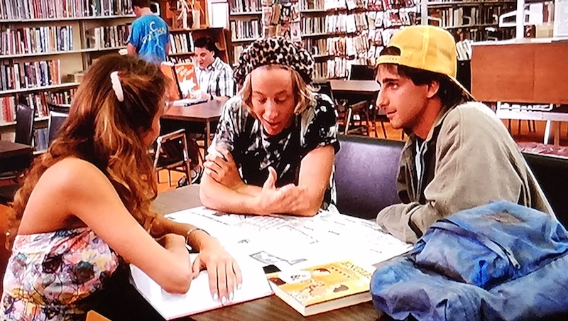 Dave, Chainsaw, and Anna-Maria in the school library in a scene from Summer School
