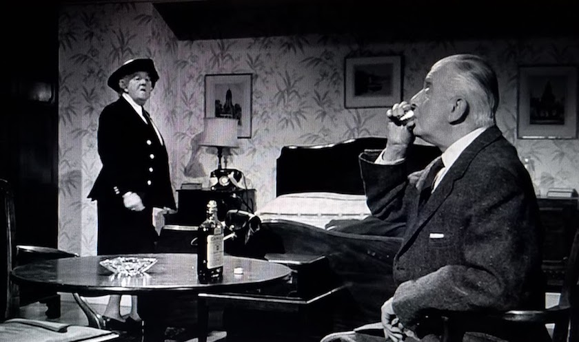 Mr. Stringer sips a brandy after learning he's a murder suspect, in Murder Ahoy! (1964)